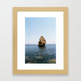 Rock and swimmers Framed Art Print
