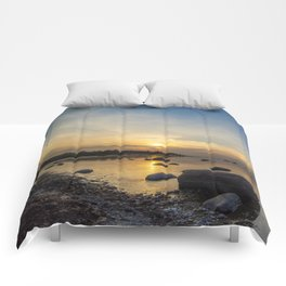 Sun with faint halo over the calm sea and reef rocks Comforters