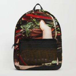 Choosing rhubarb in a grocery store Backpack