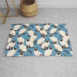 Siamese Cats crowd on blue Rug