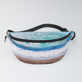 sandy beach with blue water and blue sky in summer Fanny Pack