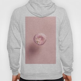 Pink doughnut with sprinkles falling or flying in motion against pink pastel background Hoody