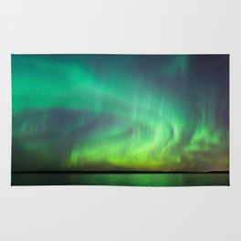 Beautiful northern lights aurora borealis over lake in Finland Rug